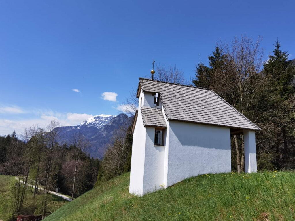Die Antoniuskapelle am Reintalersee, hinten die schneebedeckten Berge im Rofan